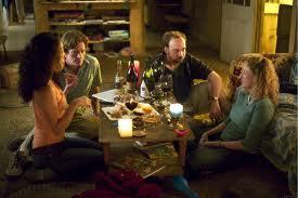 ¿No es genial esta escena? cuatro amigos relajándose en torno a una cena y vinos deliciosos